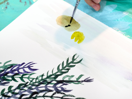 artist paints a picture with a brush with watercolors on a white sheet of paper close up