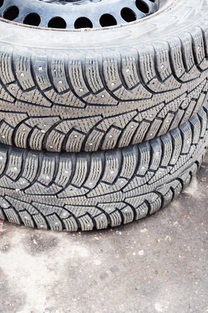 pair of old studded snow tires on ground during for seasonal replacement of wheels