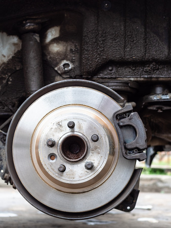 front view of new brake disc on old vehicle close up