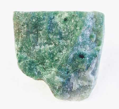 macro photography of natural mineral from geological collection - raw green aventurine stone on white background