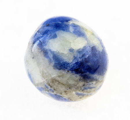 macro photography of natural mineral from geological collection - tumbled blue Sodalite gemstone on white background