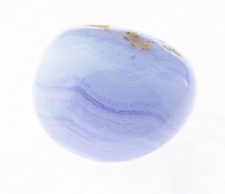 macro photography of natural mineral from geological collection - tumbled blue lace agate (chalcedony, sapphirine) gem on white background