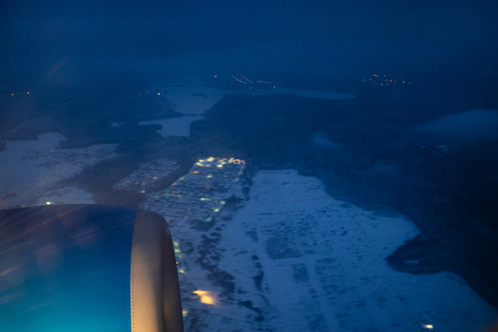 view of illuminated aircraft turbine over snow covered fields through porthole during flight in winter night (focus on the turbine) Archivio Fotografico