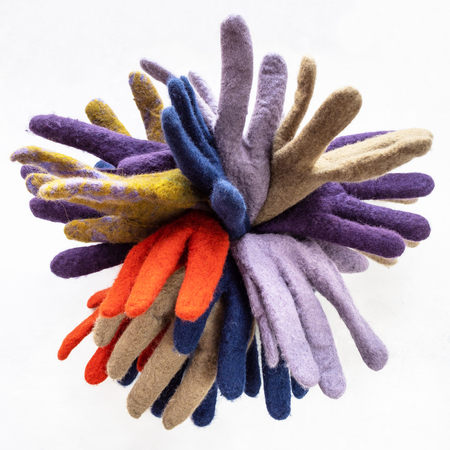 bunch of new various felted gloves on gray concrete board