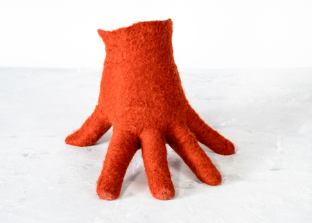 orange woolen glove stands on gray concrete board with white background 版權商用圖片