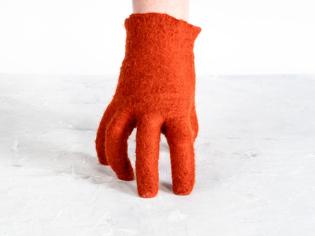 hand in orange felted glove leans on gray board with white background 版權商用圖片