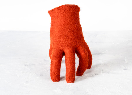 orange felted glove stands on gray board with white background