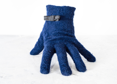 blue woolen glove with bow tie stands on gray board with white background 版權商用圖片