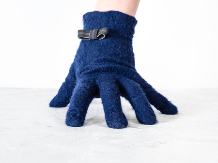 hand in blue woolen glove with bow tie leans on gray board with white background 版權商用圖片