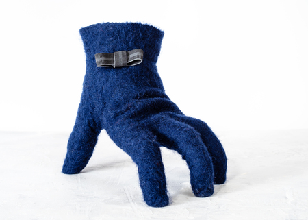 blue felted glove with bow tie stands on gray board with white background