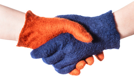 handshake of two hands in blue and orange gloves isolated on white background Stock Photo