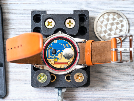 watch repairer workshop - open quartz wristwatch fixed in holder for replacing battery on wooden table