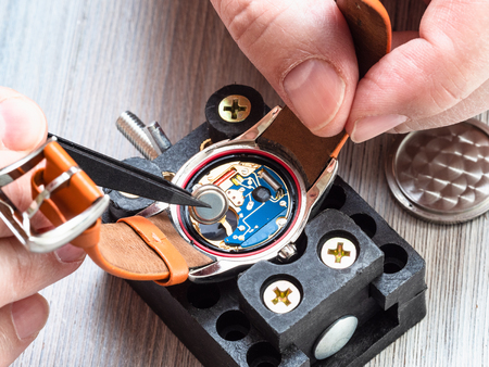 watch repairer workshop - watchmaker repairs quartz wristwatch with plastic tweezers on wooden table close up Stockfoto