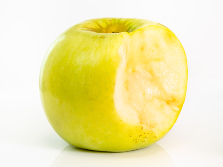 bitten yellow apple fruit on plate on white background Stock Photo