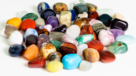 handful of various gem stones on white board