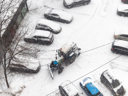above view of cleaning of parking area with tractor in residential district in snowfall in Moscow city in snowy winter day Stock Photo