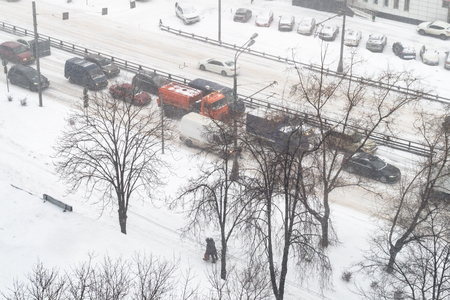 above view of cars drive in snowfall in Moscow city in snowy winter day