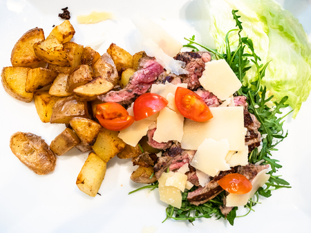 Italian cuisine - top view of Tagliata di Manzo (sliced angus roast beef) with Rustic Roasted Potatoes, Parmesan cheese and arugula salad on white plate in local restaurant in Lombardy