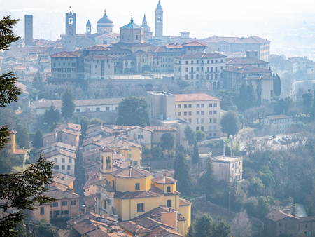 Travel to Italy - above view of Citta Alta (Upper town) of Bergamo city from San Vigilio hill in spring haze 写真素材