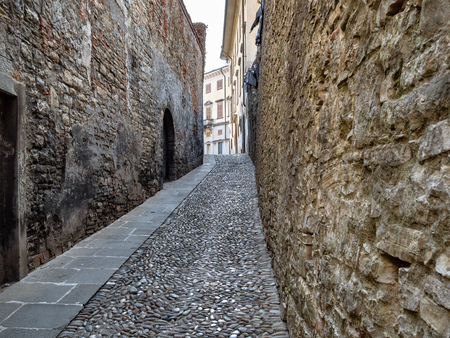 Travel to Italy - narrow street Via S Salvatore with cobblestone pavement between stone walls in Upper Town (Citta Alta) of Bergamo city, Lombardy