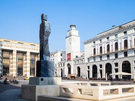 BRESCIA, ITALY - FEBRUARY 21, 2019: people near statue di Paladino and view of clock tower Torre della Rivoluzione and Palace of Post and Telegraph on Piazza della Vittoria in Brescia city.