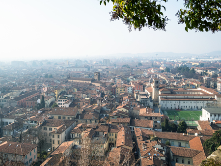 Travel to Italy - above view of Brescia city with football field and churches Santuario di Santa Maria delle Grazie and Chiesa dei Santi Faustino e Giovita from castle in spring haze