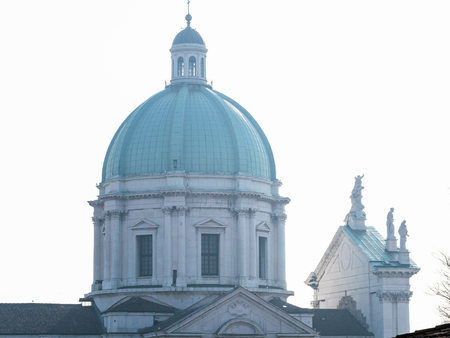 Travel to Italy - dome of Duomo Nuovo (The New Cathedral, Cattedrale estiva di Santa Maria Assunta) in Brescia city, Lombardy in spring haze