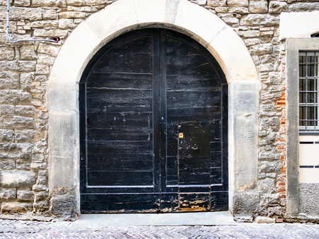 Travel to Italy - wide outdoor black wooden door in stone residential medieval urban house on old street Via Gaetano Donizetti in Upper Town (Citta Alta) of Bergamo city, Lombardy