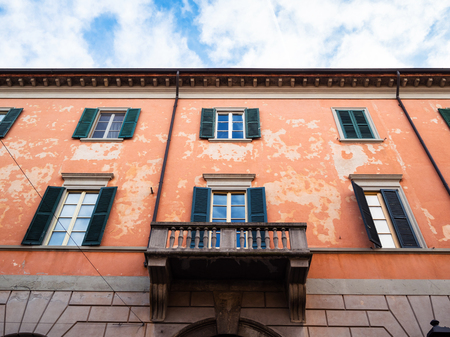 Travel to Italy - bottom view of red apartment house on street via Giovanni Battista Moroni in Lower Town (Citta Bassa) of Bergamo city, Lombardy in spring
