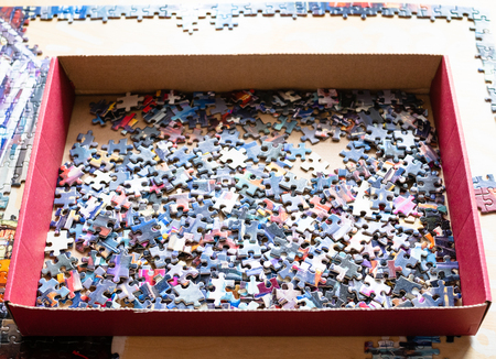 box with tiles of jigsaw puzzle on table with partly assembled puzzle