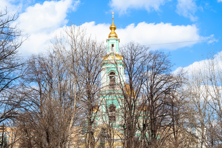 view of bell tower of Cathedral of the Epiphany in Yelokhovo in Moscow city through bare trees in public garden Elokhovskaya square in sunny spring day