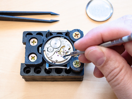 top view of watchmaker fixes mechanism of mechanical watch in holder on table in workshop close up