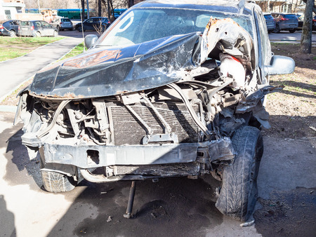 crashed car on city street in sunny spring day