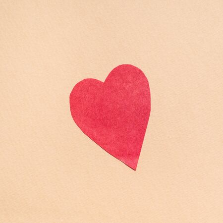one heart cut from red paper on beige paper background