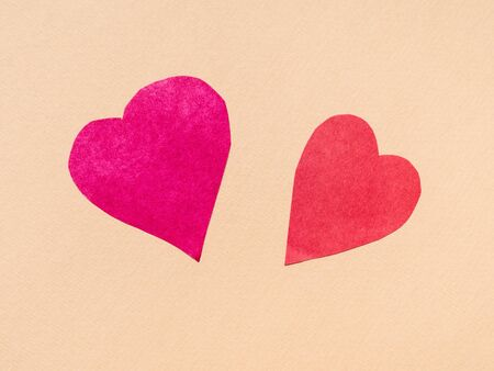 two hearts cut from red papers on beige paper background