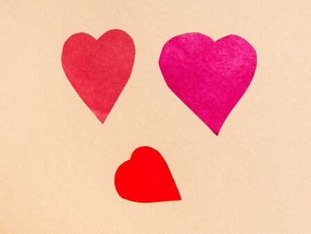 three various hearts cut from red papers on beige paper background Banco de Imagens
