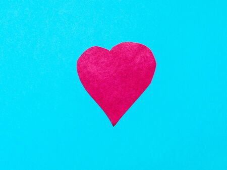 one heart cut from pink paper on blue turquoise paper background Banco de Imagens