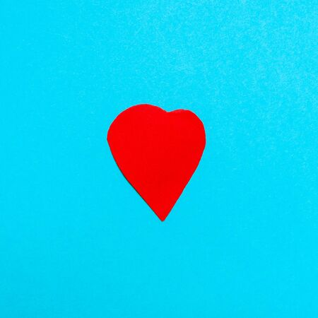 one heart cut from red paper on blue turquoise paper background