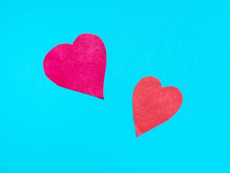 two different hearts cut from red papers on blue turquoise paper background Banco de Imagens