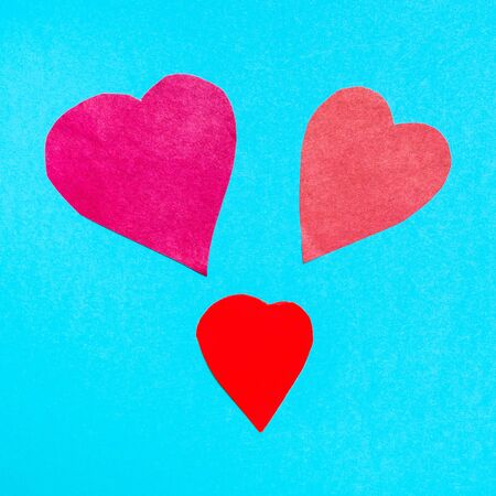 three various hearts cut from red papers on blue turquoise paper background