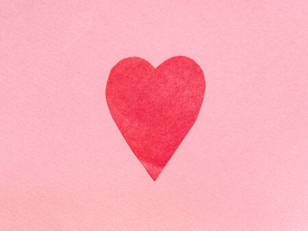 one heart cut from red paper on pink paper background