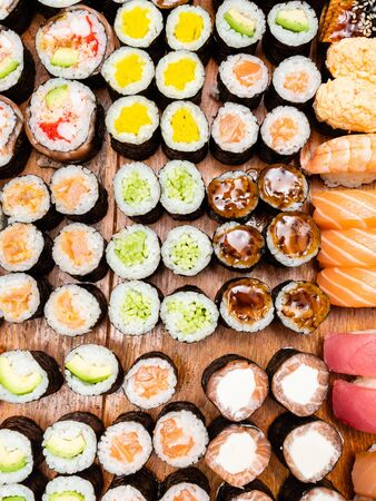 top view of many sushi and rolls on wooden table