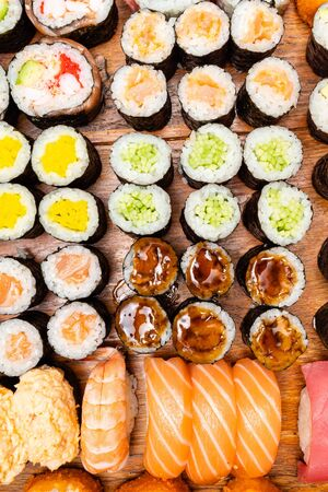 top view of big set of sushi and rolls on wooden table