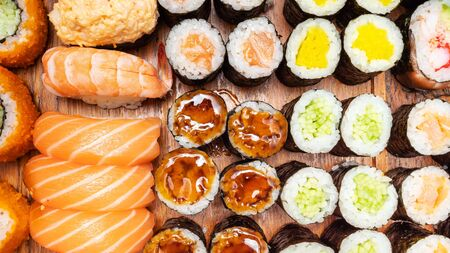 top view of lot of sushi and rolls on wooden table Stock fotó