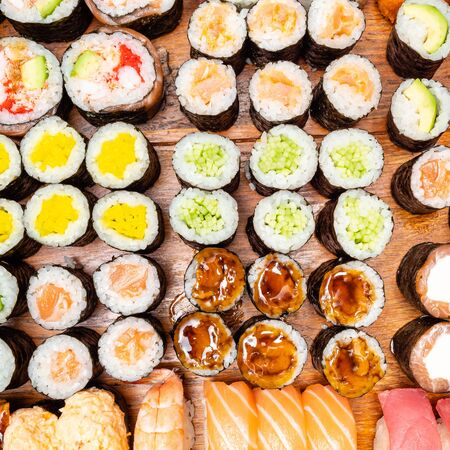 top view of different sushi and rolls on wooden table