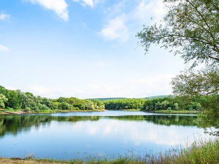 natural background - karst lake in forest in sunny summer day (Chernobayevskoye lake in Abinsky District in Kuban region of Krasnodar Krai of Russia)