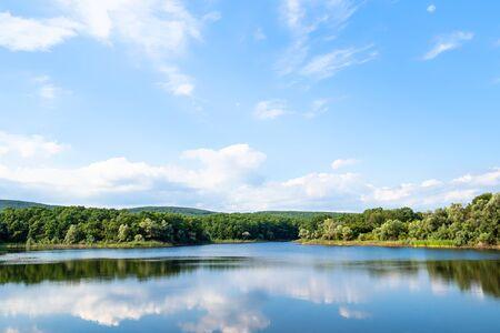 natural background - view of karst lake in green hills in calm summer evening (Chernobayevskoye lake in Abinsky District in Kuban region of Krasnodar Krai of Russia) Imagens
