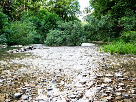 natural background - water stream flows in the stone bed of mountain river in forest in the Caucasus (Abin river in Abinsky District in Kuban region of Krasnodar Krai of Russia)