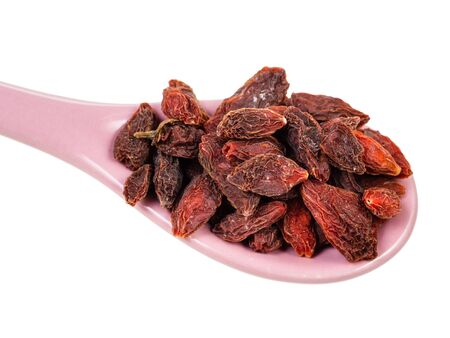 ceramic spoon with dried goji berries close-up cut out on white background Banco de Imagens