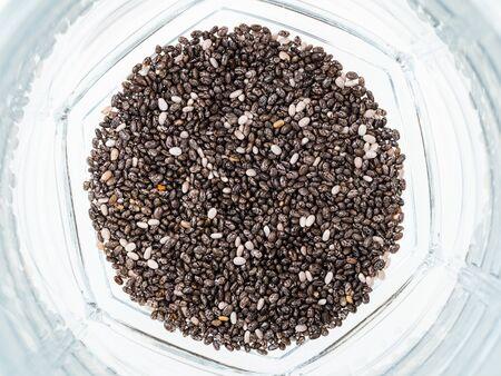 top view of handful of dry chia seeds at bottom of glass beaker Banco de Imagens